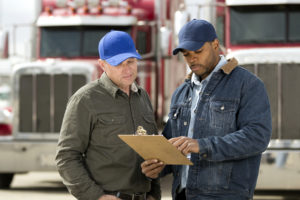 DOT inspector and flatbed driver looking at clipboard during inspection